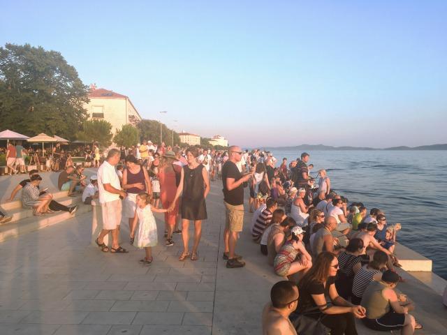 シーオルガンに座って日が沈むのを待つ人々